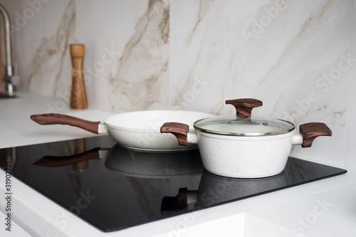 Slika na platnu Pot and pan on black induction stove in the kitchen
