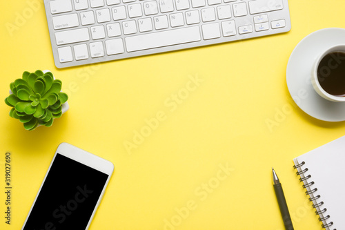 Obraz Yellow desk office with laptop, smartphone and other work supplies with cup of coffee. Top view with copy space for input the text. Designer workspace on desk table essential elements on flat lay - fototapety do salonu