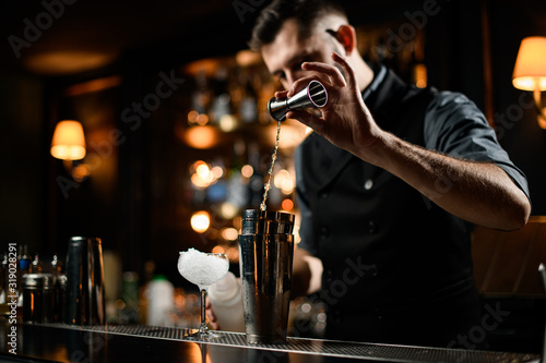 Leinwand Poster Male bartender flows alcohol from small jigger to shaker