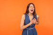 canvas print picture - Acute pain in chest. Sick overworked brunette woman clutching breast and grimacing from painful cramp, heart attack at young age, cardiac disease. indoor studio shot isolated on orange background