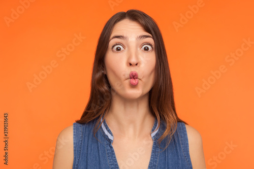 Closeup of funny stupid brunette woman making fish face, looking with big amazed shocked eyes and idiotic silly expression, showing ridiculous grimace Wallpaper Mural