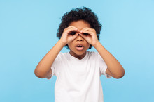 Curious Child Exploring World. Portrait Of Inquisitive Nosy Little Curly Boy Looking Through Fingers Shaped Like Binoculars And Expressing Amazement. Indoor Studio Shot Isolated On Blue Background