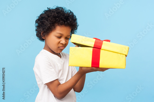 Obraz Portrait of curious adorable little boy peeking inside gift box, unpacking present with funny inquisitive look, impatient child unboxing birthday surprise. studio shot isolated on blue background - fototapety do salonu