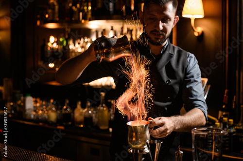 Male bartender flows burning liquid from mug to mug Wallpaper Mural
