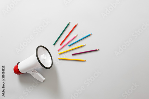 Fototapeta Megaphone with colorful pencils on white background obraz