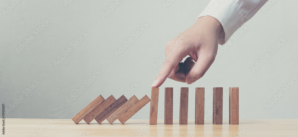 Fototapeta Hand stopping wooden domino business crisis effect or risk protection concept