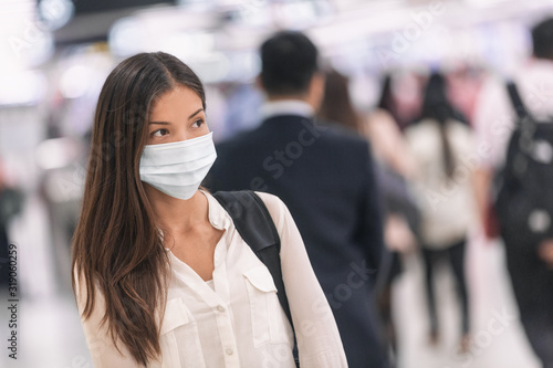 Virus mask Asian woman travel wearing face protection in prevention for coronavirus in China. Lady walking in public space bus station or airport. - 319060259