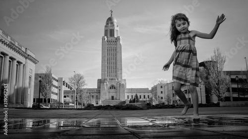 Fotografie, Obraz Cute Girl Playing On Wet Footpath Against Sky