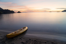 Kayak With Oar Moored On Sea Shore At Sunset