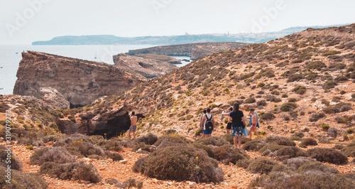 Fotografia Rear View Of People Walking On Mountain Against Sky