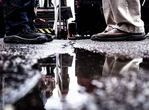 Canvas Print Low Section Of People Standing On Wet Street