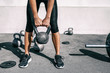 Kettlebell weightlifting athlete woman lifting weight at outdoor fitness gym. Lower body legs and feet closeup of strength training legs, glutes and back lifting free weights.