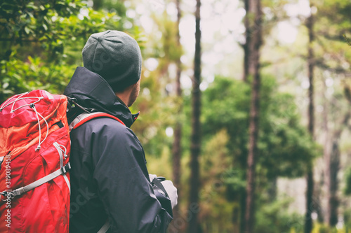 Fototapeta Hiker man hiking in forest with backpack - Camping outdoors lifestyle. Trek in wilderness winter. obraz