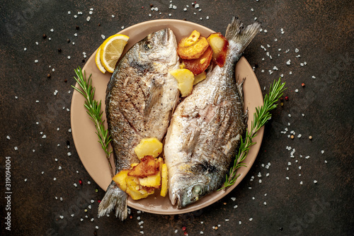 Fototapeta grilled dorado fish and fried potatoes on a plate with spices and lemon on a stone background obraz