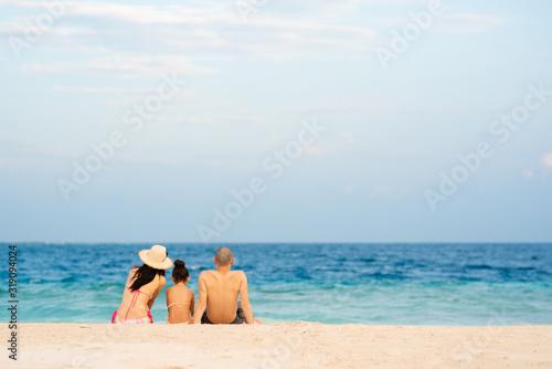 Obraz 砂浜に座る父と母と娘 - fototapety do salonu
