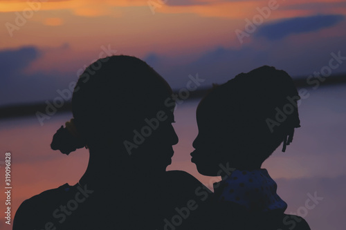 Valokuva Close-Up Of Silhouette Mother With Daughter At Beach Sky During Sunset