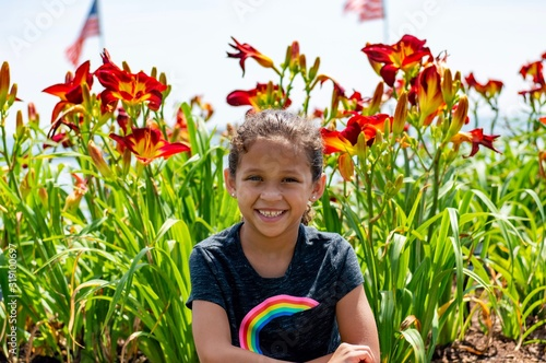 Fotografie, Tablou  Portrait Of Smiling Girl Against Flowering Plants