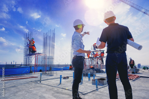 Fototapeta Structural engineer and architect working with blueprints discuss at the outdoors construction site. obraz