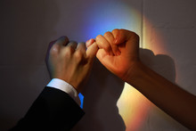 Cropped Hands Of Couple Hands Taking Pinky Promise Against Wall