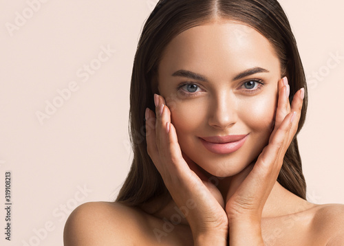 Fototapeta Beautiful woman face close up natural make up hand touching face beauty smile obraz