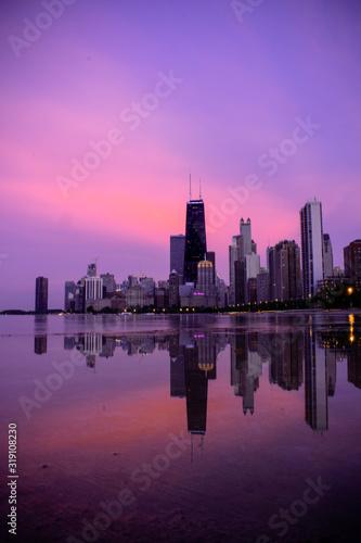 Obraz na plátne REFLECTION OF BUILDINGS IN LAKE AGAINST SKY DURING SUNSET