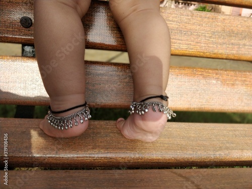 Low Section Of Baby Girl Wearing Anklets Standing On Bench Canvas Print