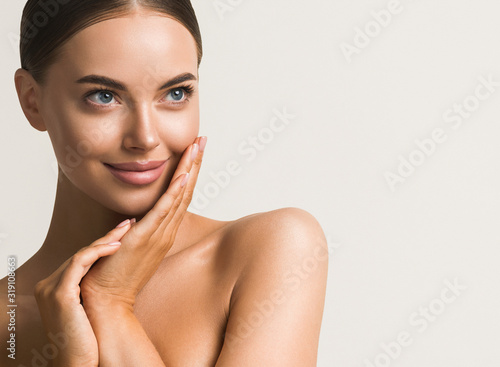Beautiful woman face close up natural make up hand touching face beauty smile Fototapet