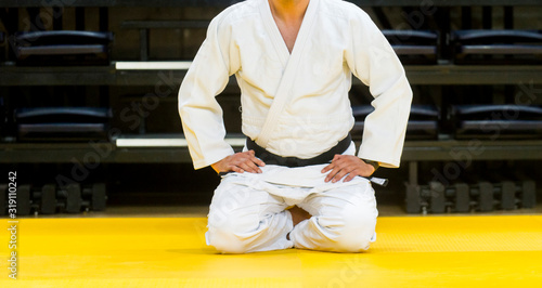 Obraz Low Section Of Male Judo Sitting On Floor Against Wall - fototapety do salonu