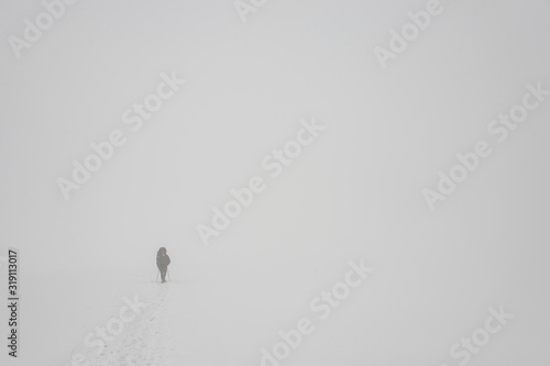 Photo Man climbing on the mountain hill with hiking sticks and backpack during the bli