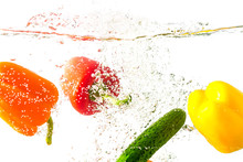 Three Bell Peppers And Cucumber Fall Into The Water With Splashes, Isolated On A White Background. Healthy Eating Concept.
