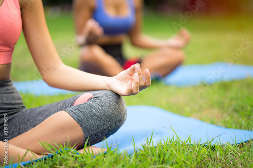 Valokuva Buddy woman training asana yoga by doing lotus pose for meditation, balance body at outdoor park with trainer