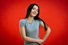 Universal Concept Of A Cute Smiling Girl On A Red Background. Portrait Of A Pretty Young Brunette Woman In A Gray T-shirt. Talking, Showing Hands With Emotions.
