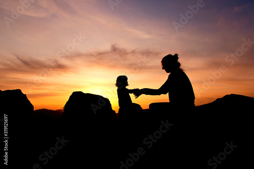 Fototapety, obrazy: Silhouette Mother And Daughter Holding Hands Against Orange Sky