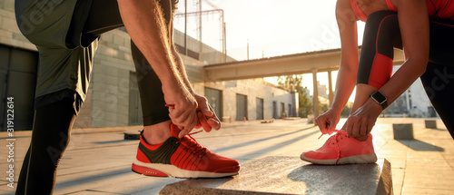 Fototapeta Active morning. Close up photo of two people in sport clothes tying shoelaces before running together outdoors obraz