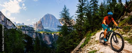 Tourist cycling in Cortina d'Ampezzo, stunning rocky mountains on the background Tapéta, Fotótapéta