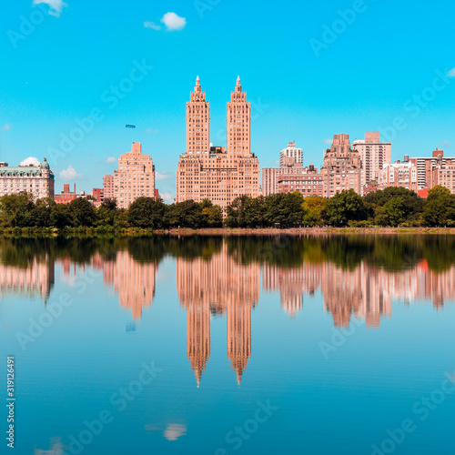 Fotografie, Obraz REFLECTION OF BUILDINGS IN LAKE AGAINST BLUE SKY