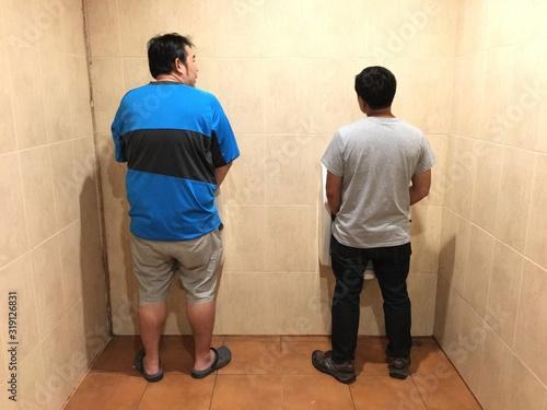 Fotografía Rear View Of Men Urinating In Public Bathroom