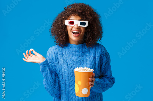 Happy amused good-looking african-american female laughing out loud, eating popc Fototapeta