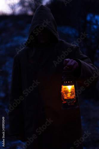 Fotografie, Obraz a man with an old glowing lantern in a raincoat in a dark forest