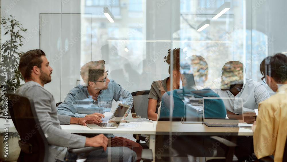 Fototapeta Setting Goals. Group of business people communicating and discussing fresh ideas while sitting together behind the glass wall in the meeting room