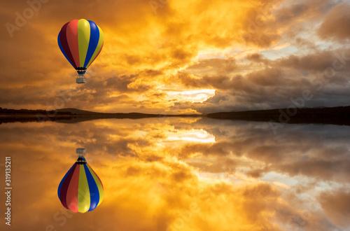 A hot air balloon over a lake at sunrise Canvas Print