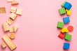 Children's wooden toys on a pink background concept zero west. Frame from developing colored cubes. Copy space. Top view