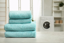 Stack Of Clean Towels On Table In Laundry Room. Space For Text