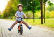canvas print picture - happy child boy rides a racetrack in Park in summer