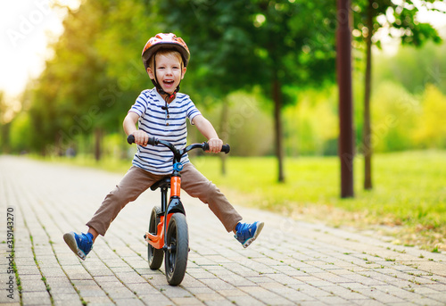 happy child boy rides a racetrack in Park in summer