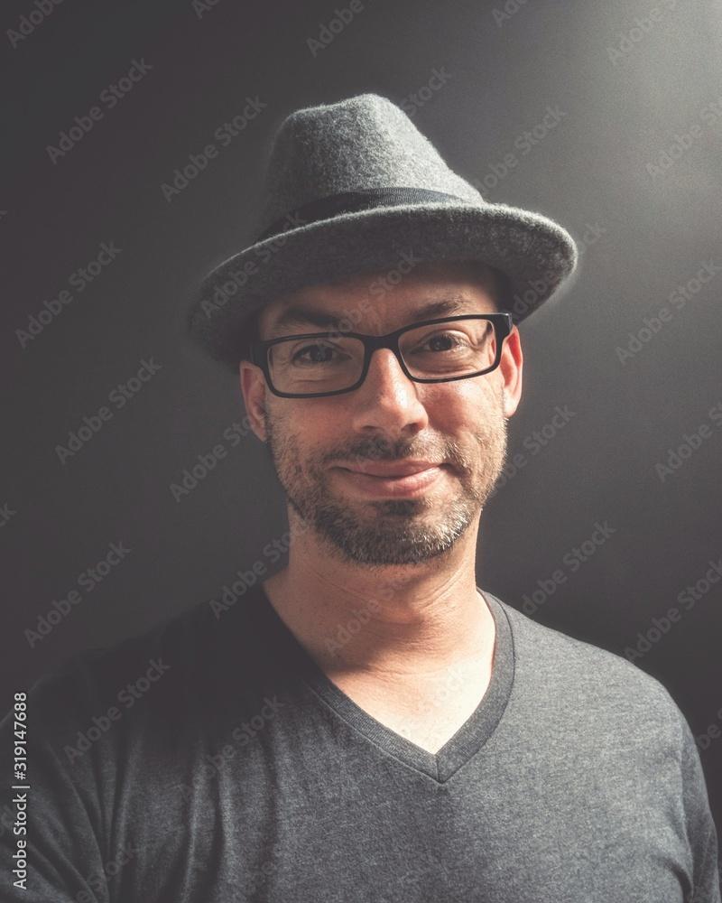 Fototapeta Close-Up Portrait Of Smiling Man Wearing Hat And Eyeglasses Against Black Background