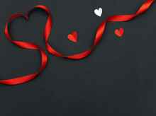 Red Heart Ribbon Shape And Hearts Paper On Black Background With Copy Space For Valentine's Day And Wedding.