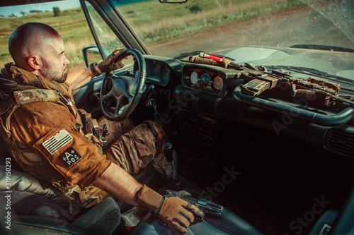 Vászonkép Bald soldier in uniform is driving military vehicle.