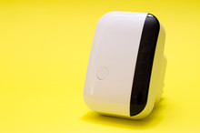 Wireless Wifi Repeater On Yellow Background Close-up