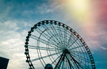 Low Angle View Of Ferris Wheel Against Cloudy Sky During Sunset